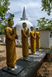 Buddhist monk statues stand near a stupa at the Pidurangala Buddhist Temple in Sigiriya, Sri Lanka. Stock Images
