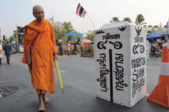 Buddhist Monk at a Street Protest in Bangkok. BANGKOK - JAN 20: An unidentified Buddhist monk walks past a mock border post as the Thai Patriots Network protest Stock Image