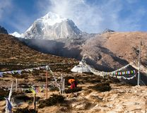 Buddhist monk, stupa and prayer flags near Pangboche. Monastery and Tabuche peak, life in Khumbu valley on the way to Everest base camp, nepal Stock Photos