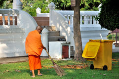 Sweeping Monk. A Buddhist monk sweeping the temple grounds at Wat Traphang Thong in the Sukhothai historical park which covers the ruins of the old city of Stock Photo