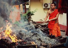 Buddhist monk tends to the laundry and a fire Stock Photo