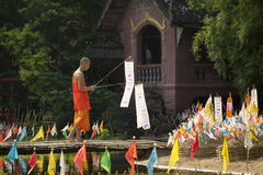 Buddhist monk with traditional flags. CHIANG MAI THAILAND - APRIL 17 : Songkran festival, Buddhist monk pin traditional flags on sand pagoda. APRIL 17,2014 in stock image