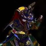 A Buddhist monk in traditional Tibetan robes performs a sacred Dance of Black Hats. Buddhist monk in traditional Tibetan robes performs a sacred Dance of Black Royalty Free Stock Photo