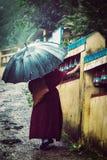Buddhist monk with umbrella spinning prayer wheels Stock Photo