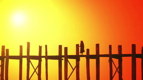 Buddhist monk walking across U Bein Bridge sunset silhouette. Amarapura, Myanmar (Burma) stock video footage