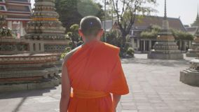 Buddhist monk walking alone on the street stock video