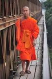 Buddhist monk walking on the bridge. 05/12/2009 Buddhist monk walking on the bridge , Lao PDR Stock Photo