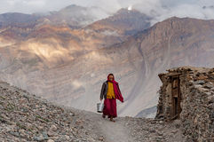 Buddhist monk walking road mountain village India clouds Royalty Free Stock Images