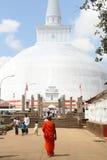 Buddhist monk and white stupa Stock Photos