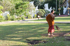 Buddhist monk working with broom sweeps lawn from fallen leaves Royalty Free Stock Photography