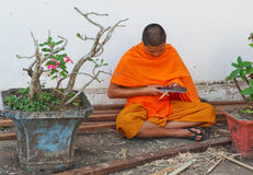 Buddhist Monk works with a knife and wood. Luang Prabang. Laos. Stock Photography