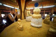 Buddhist Monk worship Five small golden Buddhas. Stock Photo