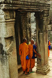 Buddhist monks in Angkor Wat, Cambodia, at pillars. Buddhist monks at a temple in Angkor Wat, Cambodia, sightseeing at ancient tourist attraction, walking along Stock Photography