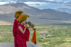 Buddhist monks blowing into a Tibetan specific instrument at th royalty free stock image