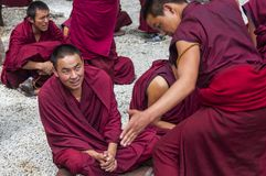 Buddhist monks` debating practice ,one monk is clapping , drastic debating , Tibet stock photography