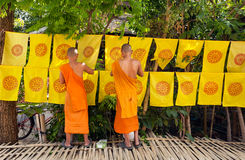 Buddhist monks decorated by flags with religious symbols all area outside monastery Stock Photos
