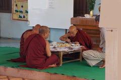 Buddhist monks eating Stock Images