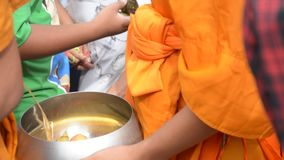 Buddhist monks are given food offering from people for End of Buddhist Lent Day stock video footage