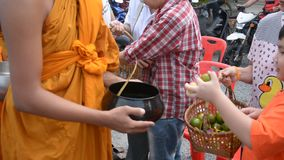 Buddhist monks are given food offering from people for End of Buddhist Lent Day stock video