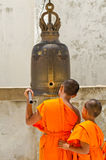 Buddhist monks hit the bell to prayer. Royalty Free Stock Image