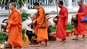 Buddhist monks in Luang Prabang , Laos. LUANG PRABANG, LAOS - JUNE 4, 2019: Tak Bat Ritual Ceremony in the Mornings - Buddhist monks receive rice and food from stock video footage