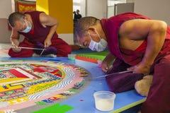 Buddhist monks making mandala from coloured sand Royalty Free Stock Image