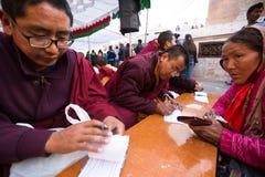 Buddhist monks near stupa Boudhanath during festive Puja of H.H. Drubwang Padma Norbu Rinpoche's reincarnation's. Unidentified tibetan Buddhist monks near stupa royalty free stock images
