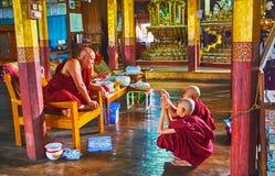 Buddhist monks in old monastery on Inle Lake, Myanmar. INLE LAKE, MYANMAR - FEBRUARY 18, 2018: The bhikkhu Buddhist monk teaches the young samaneras novice monks Stock Image