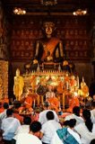 Buddhist monks praying during an afternoon ceremony at their wat stock photo