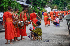 Buddhist monks daily ritual of collecting alms and offerings Stock Image