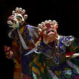 Buddhist monks in ritual tantric costumes bright colors and ancient masks on a black background. Royalty Free Stock Photos