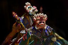 Buddhist monks in ritual tantric costumes White Mahakala and Orange Makara on black background. Stock Images