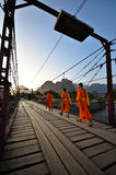 Buddhist monks and rusty bridge Stock Photos