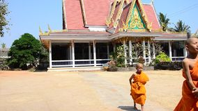 Buddhist monks and Samanen or a novice monk. In a Buddhist context walking at Wat Pho Sri Sa-at of Pon ngoy Village on February 8, 2015 in Surin Thailand stock footage