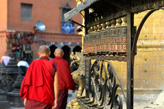 Buddhist monks spinning the prayer wheels Royalty Free Stock Images