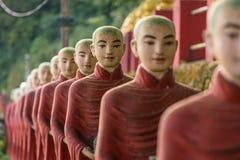 Buddhist monks stone statues row at Kaw Ka Thaung cave stock photos