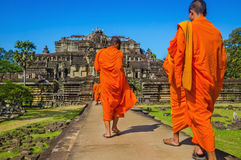 Buddhist monks in traditional orange robes stock images
