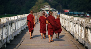 Buddhist monks. Unrecognized Buddhist monks walking on U Bein Bridge Royalty Free Stock Image