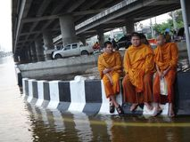 Buddhist monks are waiting by a flooded street of Pathum Thani in October 2011.  Stock Image