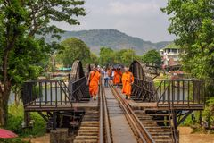 Buddhist monks walk on the bridge over the river Kwai in Thailand Royalty Free Stock Images