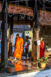 Buddhist monks walk through a temple within the Temple of the Sacred Tooth Relic complex in Kandy in Sri Lanka. Stock Photos