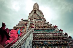 Buddhist monks walk up stairs of Wat Arun temple in Bangkok Stock Photography