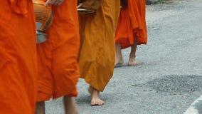 Buddhist monks walking barefoot along the street. Buddhist monks walking barefoot along the street in Luang Prabang, Laos stock footage