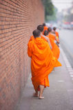 Buddhist Monks walking. To receive food through the Wall Royalty Free Stock Photos