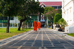 Buddhist novice monks in bright orange robe casually walking Stock Images