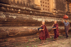 Buddhist novice monks walking alms in Bagan. Southeast Asian young Buddhist novice monks walking morning alms in Old Bagan, Myanmar Royalty Free Stock Photos