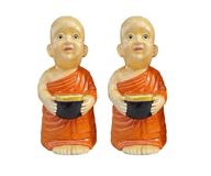 Buddhist novice resin characters holding alms bowl in hand isolated on white background. Buddhist novice characters holding alms bowl in hand isolated on white stock images
