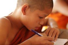Buddhist novice studying in Luang Prabang, Laos. Young Buddhist novice studying at a monastic school in Luang Prabang, Laos royalty free stock photo
