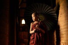 Buddhist novice walking with umbrella stock image
