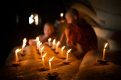 Buddhist novices with candle light inside temple Royalty Free Stock Image